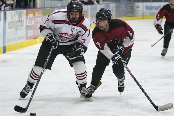 Mankato West's Courtney Bloemke (left) carries the puck deep into the offensive zone while being defended by Fairmont's Brooklyn Meyer. Bloemke had four points in the Scarlets 9-0 win. Photo by Jackson Forderer
