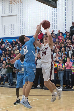 New Ulm Cathedral's Alex Hillesheim has his shot tipped by Minnesota Valley Lutheran's Jace Marotz in the second half of Friday's game. Hillesheim scored his 1,000th point for the Greyhounds early in the first half. Photo by Jackson Forderer
