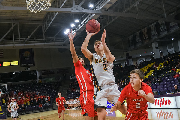 Mankato East's Jax Madson puts up a shot past Mankato West defenders Tyler Makela (right) and Mehki Collins during the annual East versus West games played at Bresnan Arena. Photo by Jackson Forderer