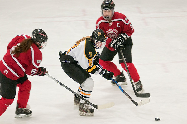 Mankato East's Madison Davis (2) skates past Kiera Swenson (6) and Sydney Morales of Mankato West. The Cougars won the Section 3A game to advance to the section final game against Marshall. Photo by Jackson Forderer