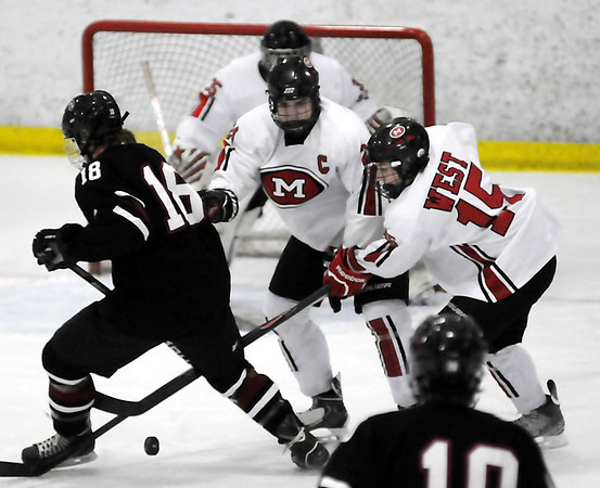John Cross<br /> New Prague's Austin Kilian tries to get the puck past Mankato West's Max Mettler (center) and Kyle Looft during first period action  at All Seasons Arena on Saturday.