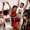 John Cross<br /> Mankato West's Tyler Stoffel gets sandwiched between a pair of Rochester John Marshall defenders during first period action at West High School on Friday.