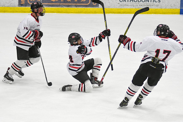 Mankato West's Blake Waletich (center) celebrates after scoring a goal against St. Paul Academy and Summit in the third period of Saturday's game. Waletich's goal tied the game and started the comeback for the Scarlets. Photo by Jackson Forderer