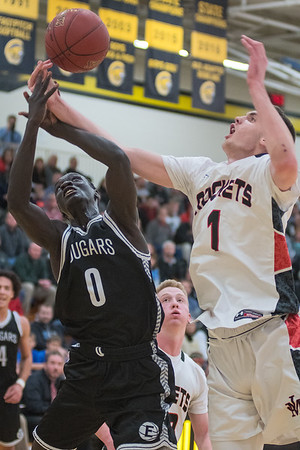 Edmon Oyet (0) of Mankato East fights for a rebound against Rochester John Marshall's Matthew Hurt (1) during the first half of Thursday's game. East pulled away in the second half to remain undefeated. Photo by Jackson Forderer