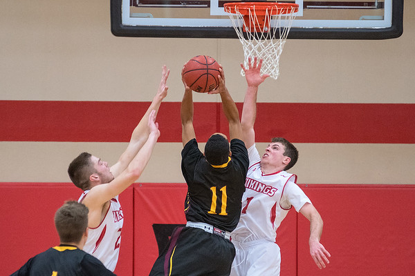 Bethany Lutheran's Neil Eichten (right) and Trenton Krueger (left) defend their basket during a drive by University of Morris' CD Douglas (11). Photo by Jackson Forderer