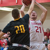 Bethany Lutheran's Trenton Krueger (21) goes up for a shot against University of Minnesota Morris' Jeffrey Halverson (20) in the second half of Wednesday's game. The Vikings defeated the Cougars in a highly offensive game. Photo by Jackson Forderer