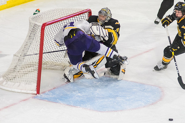 Charlie Spooner of Minnesota State flies into the Michigan Tech goal and goalie, Matt Jurusik after Spooner was hit from behind by Michigan Tech's Seamus Donohue (right) in the second period. Spooner was awarded a penalty shot on the play. The Mavericks won 4-2 for a sweep of the Huskies. Photo by Jackson Forderer