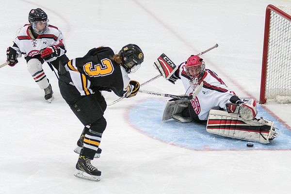Mankato West goalie Sarah Olsen makes a pad save on Mankato East's Kaylee Eykyn as Claire Johnson looks on in the second period of Thursday's game. Photo by Jackson Forderer