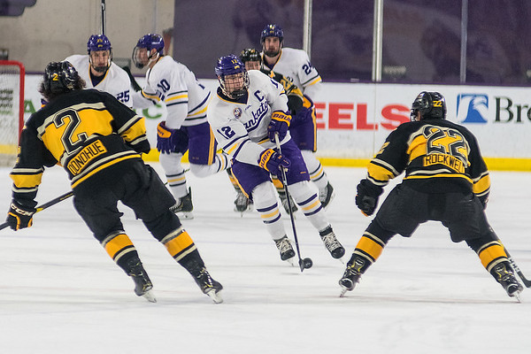 Minnesota State's Max Coatta brings the puck up the ice while Michigan Tech defenders Seamus Donohue (2) and Tyler Rockwell (22) wait for Coatta's next move in the first period of play during Saturday's game. Photo by Jackson Forderer