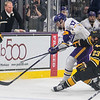 Minnesota State's Walker Duehr dumps the puck into the offensive zone as Michigan Tech's Raymond Brice slides into him during Saturday's game. Photo by Jackson Forderer