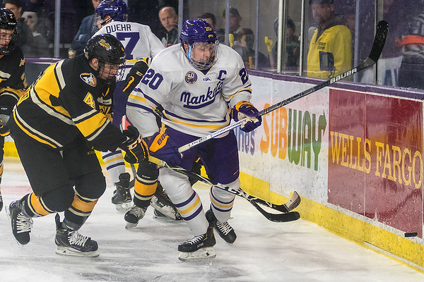 Minnesota State's Marc Michaelis (right) and Michigan Tech's Andrew Bellant scramble for the puck along the boards in the second period of play during Saturday's game. The Mavericks swept the Huskies to remain undefeated at home. Photo by Jackson Forderer