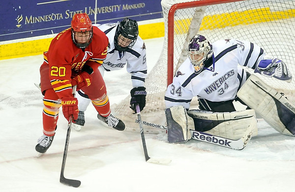 Pat Christman<br /> Ferris State's Gerald Mayhew looks to shoot around Minnesota State's Carter Foguth and goalie Cole Huggins during the first period Friday at the Verizon Wireless Center.