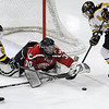 Pat Christman<br /> Mankato West goalie Maggie Cusey dives to cover the puck before Mankato East/Loyola's Taylor Kanstrup (9) and Gina Stoner (8) can get to it during the first period Tuesday.