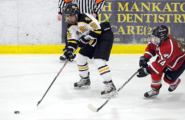 Pat Christman<br /> Mankato East/Loyola's Rebekah Kolstad passes the puck ahead of Mankato West's Callie Looft during the first period Tuesday.