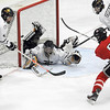 Pat Christman<br /> Mankato West's Zachary Erickson slips the puck past a sprawling Mankato East/Loyola goalie Will Behsman during the first period Tuesday at All Seasons Arena.