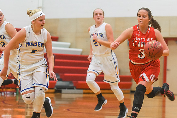 Mankato West's Emily Veroeven (3) dribbles up the court while being defended by Waseca's Taylor Hiller in the Scarlets first game of the 2017-18 season. Photo by Casey Ek