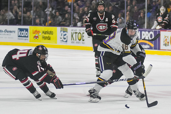 Minnesota State's Ian Scheid (right) tries to keep the puck away from the outstretched defense of St. Cloud State's Patrick Newell in a game played on Oct. 7, 2017. The two teams will face off again for Hockey Day Minnesota 2018 in St. Cloud on Saturday. Photo by Jackson Forderer