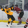 Mankato East/Loyola's Sam Schulz (left) absorbs a hit from New Prague's Caleb Smith during the second period as both teams became more aggressive with their checking. Photo by Jackson Forderer