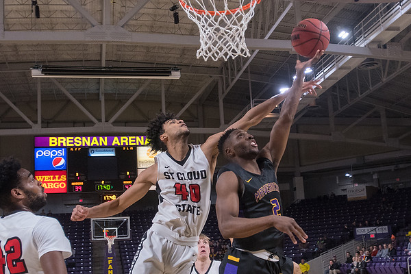 Minnesota State's Carlos Anderson shoots a reverse layup past the outreached arm of St. Cloud State's Sean Smith in the second half of Saturday's game. Photo by Jackson Forderer