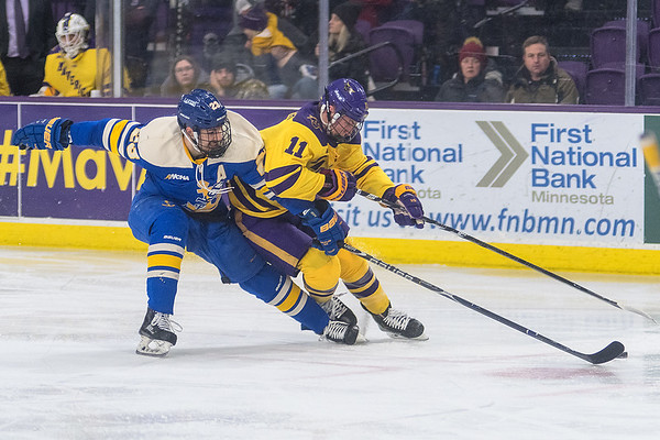 Minnesota State's Jared Spooner (right) and Lake Superior State's Collin Saccoman race for a loose puck in MSU's offensive zone in the second period of Friday's game. Photo by Jackson Forderer
