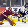 University of Minnesota goalie Adam Wilcox pokes the puck away from Minnesota State's Brett Knowles during the first period Saturday at the Verizon Wireless Center.