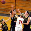 Austin's Steph Justice (11) passes out of the triple team of Mankato East's Hannah Whitington (24), Allison Taylor (52) and Claire Ziegler (44) during the first half Tuesday at the East gym.