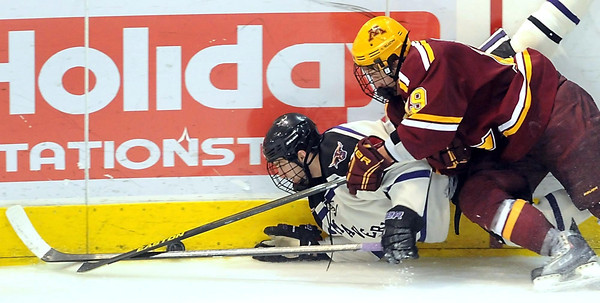 Minnesota State's Evan Mosey pushes the puck ahead as he is hit by Minnesota's Erik Haula during the second period Saturday at the Verizon Wireless Center.