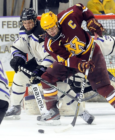 Minnesota State's Brett Stern defends Minnesota's Nate Budish in front of the goal during the first period Saturday at the Verizon Wireless Center.