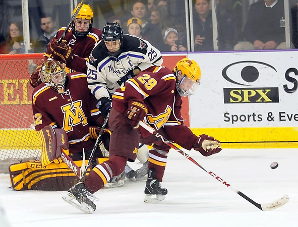 Minnesota's Nate Schmidt (29) pushes the puck away from Minnesota State's Eriah Hayes (25) during the first period Saturday at the Verizon Wireless Center.