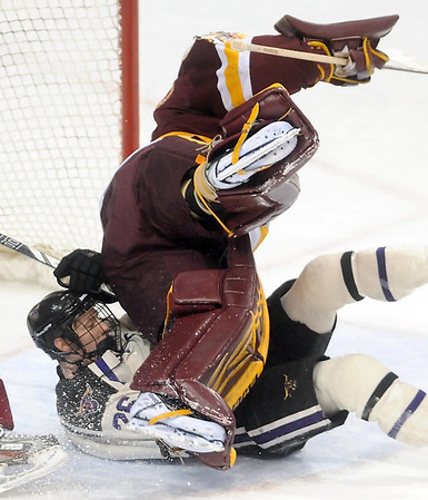 Pat Christman<br /> University of Minnesota Duluth goalie Aaron Crandall falls over Minnesota State's Dylan Margonari during the second period Friday at the Xcel Energy Center in St. Paul.