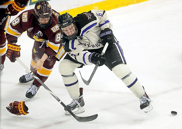 Pat Christman<br /> University of Minnesota Duluth's Kyle Osterberg loses his glove as he chases down Minnesota State's Casey Nelson during the first period of their North Star College Cup game Friday at the Xcel Energy Center in St. Paul.