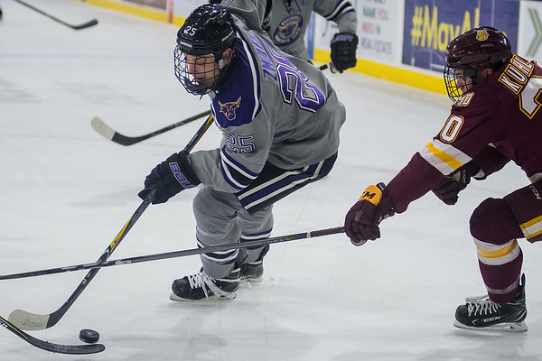 Minnesota State's Riese Zmolek gets the puck deep in the offensive zone while being defended by University of Minnesota-Duluth's Karson Kuhlman in the first period of action on Tuesday. Photo by Jackson Forderer