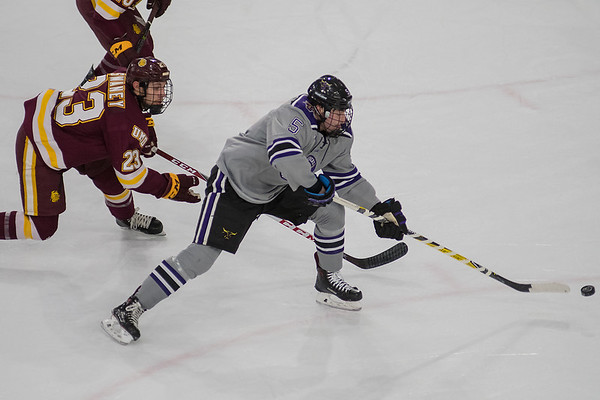 Minnesota State's Jake Jaremko (right) takes a backhand shot on net while being chased by University of Minnesota-Duluth's Nick Swaney. The Mavericks lead the game 1-0 after two periods of play in a tightly defended game. Photo by Jackson Forderer