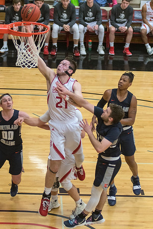 Bethany Lutheran's Trenton Krueger gets past Northland College's Benjamin Arqueros for a layup in the second half of Saturday's game. Bethany fought off a late rally by the Jacks to win 93-85. Photo by Jackson Forderer