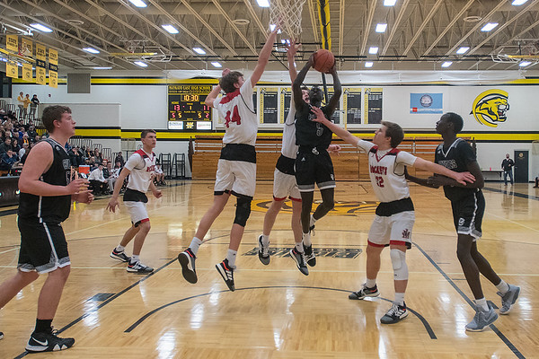 Mankato East's Joich Gong (center) drives the lane and goes up for a shot against, from left, Rochester John Marshall's Lincoln Meister (44), Matthew Hurt and Brady Black during Friday's Big Nine conference game played at East. Photo by Jackson Forderer