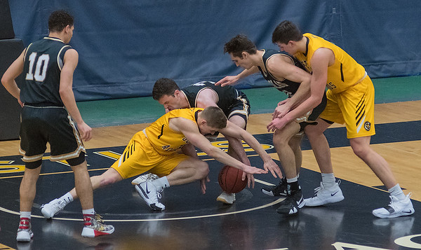 Gustavus' Logan Rezad and St. Olaf's Noah Beck fight for a loose ball in the second half of play in Wednesday's MIAC conference game. Photo by Jackson Forderer