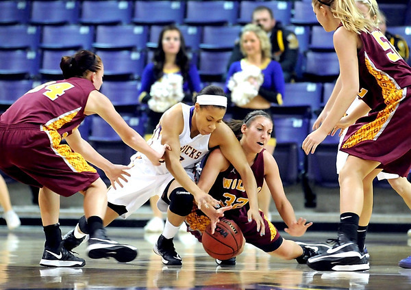 Minnesota State University's Jamelia Hudnel (left) and Northern State's Alison Kusler fall to the floor as they scramble for a loose ball during the first half Friday at Bresnan Arena.