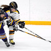 University of Wisconsin-Stevens Point's Michelle Lunneborg (12) and Gustavus Adolphus College's Kelly Thotland reach for the puck during the second period Saturday in St. Peter.