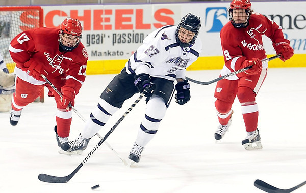 Minnesota State's Brett Stern pushes the puck ahead as Wisconsin's Nic Kerdiles (17) and Mark Zengerle (9) pursue him during the first period Friday at the Verizon Wireless Center.