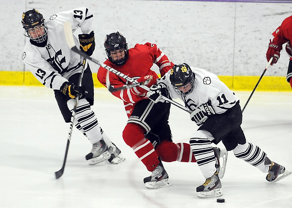 Mankato West's Galt Goettl (9) gets squeezed between Mankato East/Loyola's Brent Adams (13) and Carter Johnson (11) during the first period Thursday at All Seasons Arena.