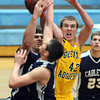 Pat Christman<br /> Gustavus Adolphus College's Brody Ziegler reaches for a reboud above a pair of Carleton defenders during the first half Saturday in St. Peter.
