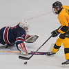 Layton Liffrig of Mankato East dekes past Albert Lea goalie Calen Hoelscher and would score the Cougars' first goal of Tuesday's game played at All Seasons Arena. The Cougars won in overtime 2-1. Photo by Jackson Forderer