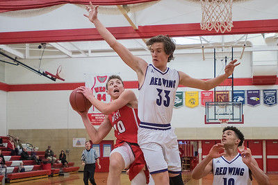 Mankato West's Griffin Corbett tries to put a shot up past Red Wing's Christian Connelly (33) during the second half of Friday's game played at West. West won the Big 9 conference game over the Wingers. Photo by Jackson Forderer
