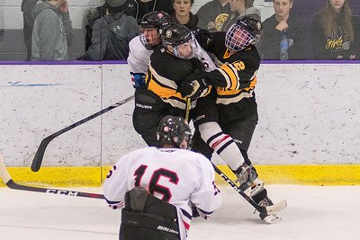 Mankato West's Stephen Schwartz is sandwiched by Mankato East's Hayden Guillemette (left) and Jackson Keller (right) during Tuesday's game. The Cougars won the game 4-3.  Photo by Jackson Forderer
