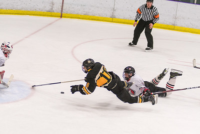 Mankato East/Loyola's Sam Schulz (center) is tripped up on a break away by Mankato West's Wyant Fowlds in the second period of Tuesday's game played at All Seasons Arena. Schulz was awarded a penalty shot, which was stopped by West goalie Wenninger (left). Photo by Jackson Forderer