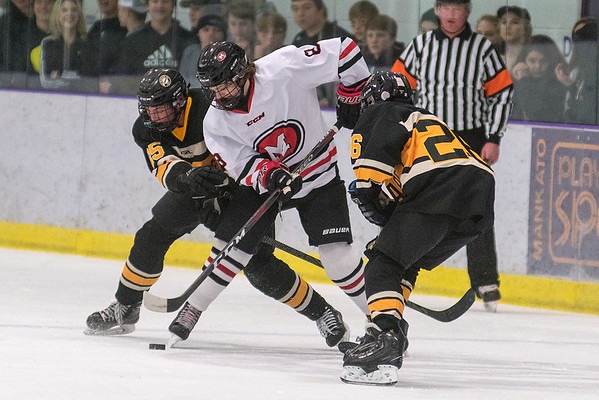 Mankato West's Drew Steiert handles the puck between two Mankato East/Loyola defenders Mason Pin-Bowder (right) and Parker Steindl (left) during Tuesday's boys hockey game played at All Seasons Arena. The Cougars scored two goals in the third period to break a 2-2 tie and won 4-3. Photo by Jackson Forderer