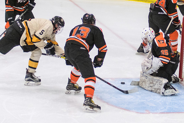 Mankato East/Loyola's Nolan Michels (left) and Winona's Eric Paulson (13) lunge for a loose puck in front of Winona goalie Campbell Watkins in the second period of Thursday's game. Photo by Jackson Forderer