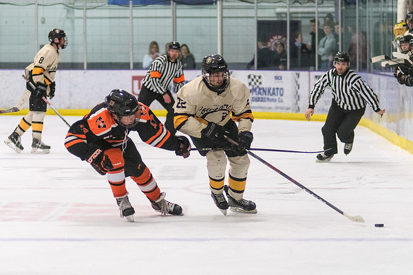 Mankato East's Layten Liffrig (right) chases the puck into the offensive zone while being defended by Winona's Hans Larsen (left) during Thursday's game played at All Seasons Arena. Photo by Jackson Forderer