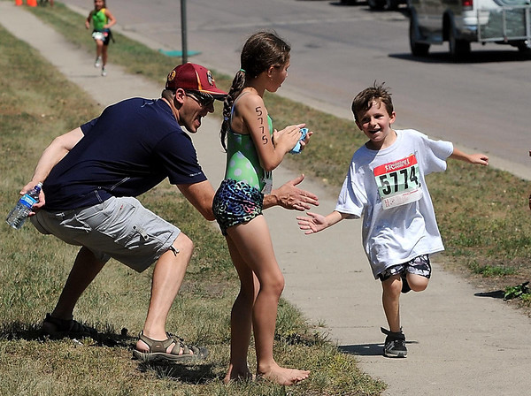 Tony Coatrella, 6, gets a high five from his father Nick and his sister Alice as he runs toward the finish line during Saturday's North Mankato Kids Triathlon.