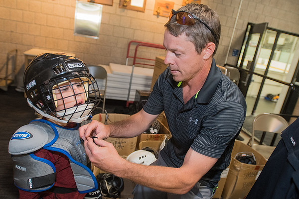 Jeff Throldahl (right), the equipment manager for the Bulldogs Association, straps on a helmet for Brayden Rothenberger, 7, outside of Gustavus' hockey rink. Children of varying levels of experience on the ice suited up and played hockey for free on Tuesday evening. Photo by Jackson Forderer